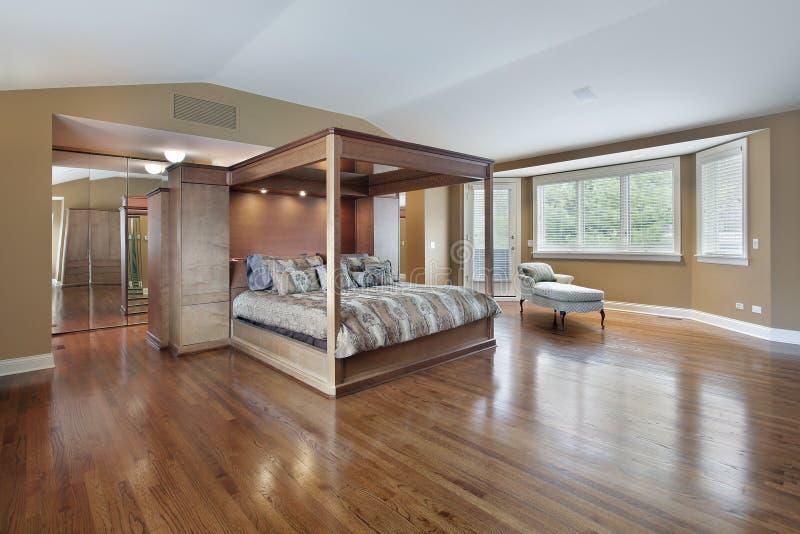 Спальня хозяев с кроватью обрамленной древесиной стоковое изображение