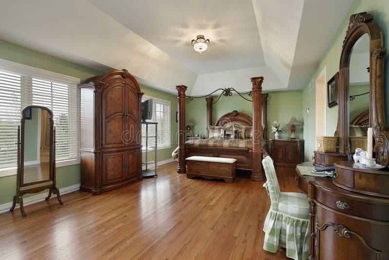 Спальня хозяев с кроватью обрамленной древесиной стоковые фотографии rf