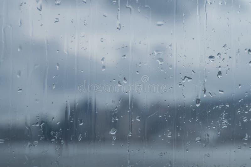 Специализированная часть окна с дождем падает через что панорама большого города и неба с облаками видима, современный город стоковое фото rf