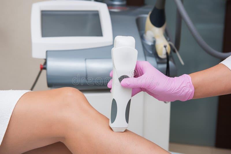 Специалист делает измерения тона кожи на ноге женщины стоковое изображение