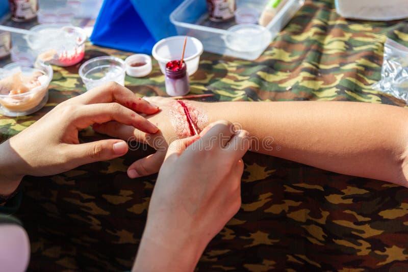 Специалист для того чтобы сделать поддельными ранами поддельные раны на оружиях детей стоковая фотография
