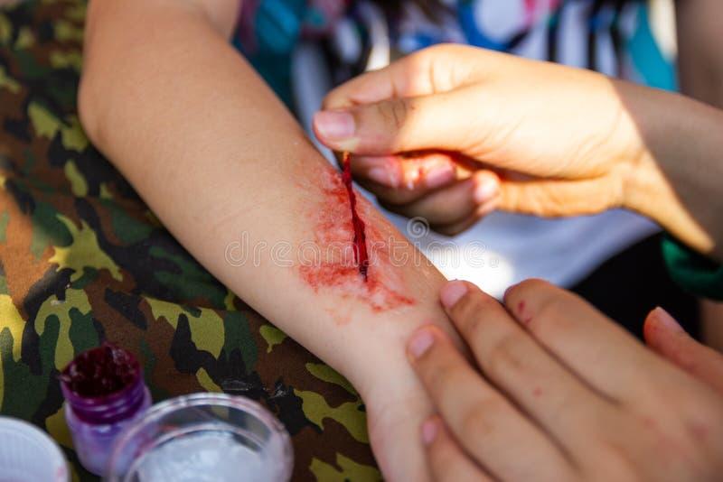 Специалист для того чтобы сделать поддельными ранами поддельные раны на оружиях детей стоковые фотографии rf