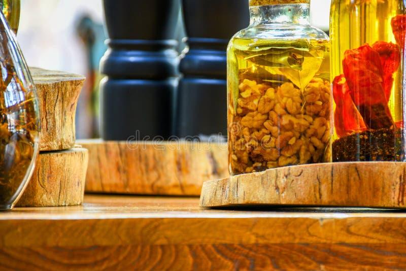 Специи и ингридиенты трав в декоративных стеклянных бутылках, украшении кухни стоковые изображения