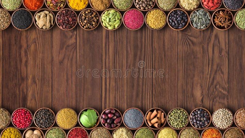 Специи и травы на предпосылке таблицы с пустым космосом для еды o стоковая фотография rf