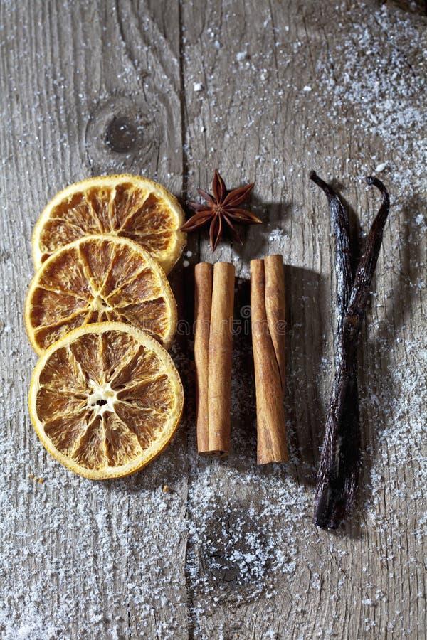 Специи рождества, высушенные оранжевые куски, ручки циннамона, анисовка звезды, ванильные фасоли на деревянной предпосылке стоковое изображение