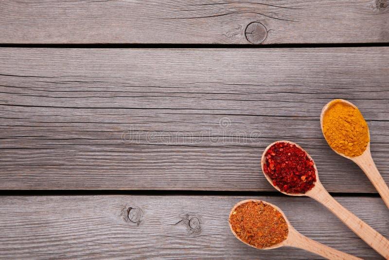 Специи смешивают на деревянных ложках на серой деревянной предпосылке Взгляд сверху стоковые фото