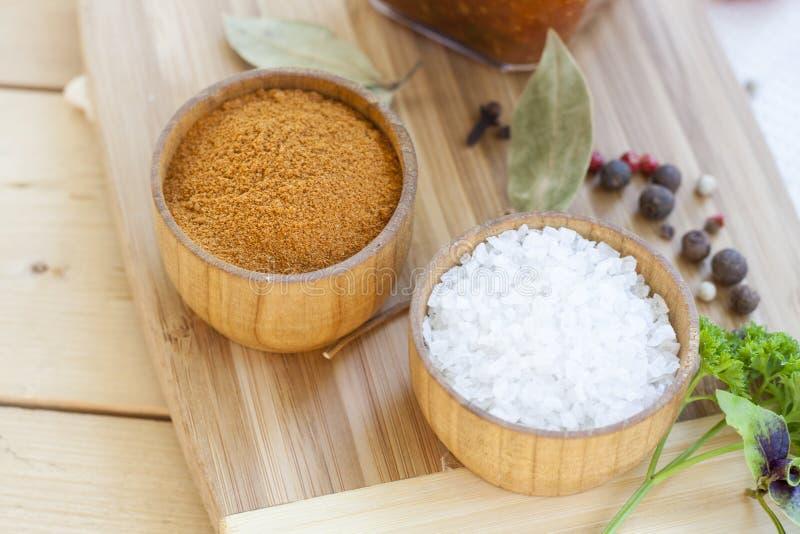 Специи: соль и перец в деревянном баке с томатами и концом-вверх трав стоковое изображение
