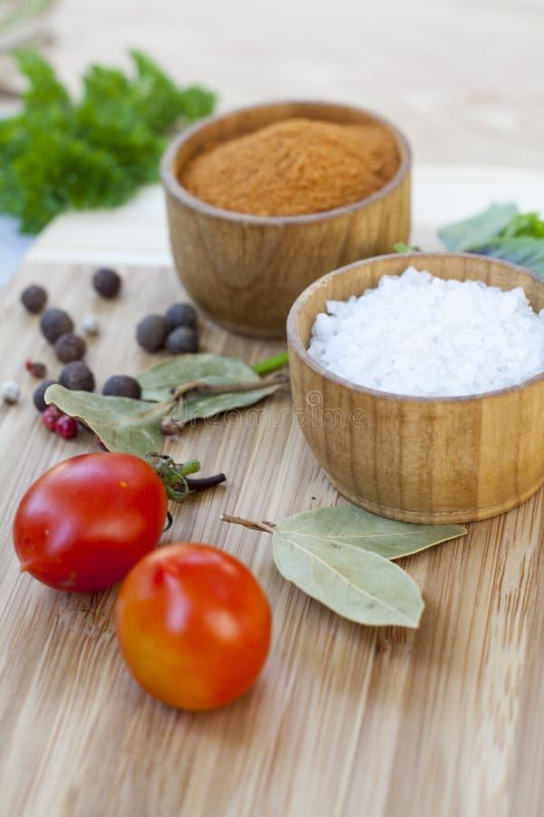 Специи: соль и перец в деревянном баке с томатами и концом-вверх трав стоковые фотографии rf