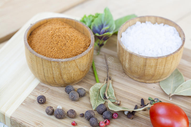 Специи: соль и перец в деревянном баке с томатами и концом-вверх трав стоковые фото