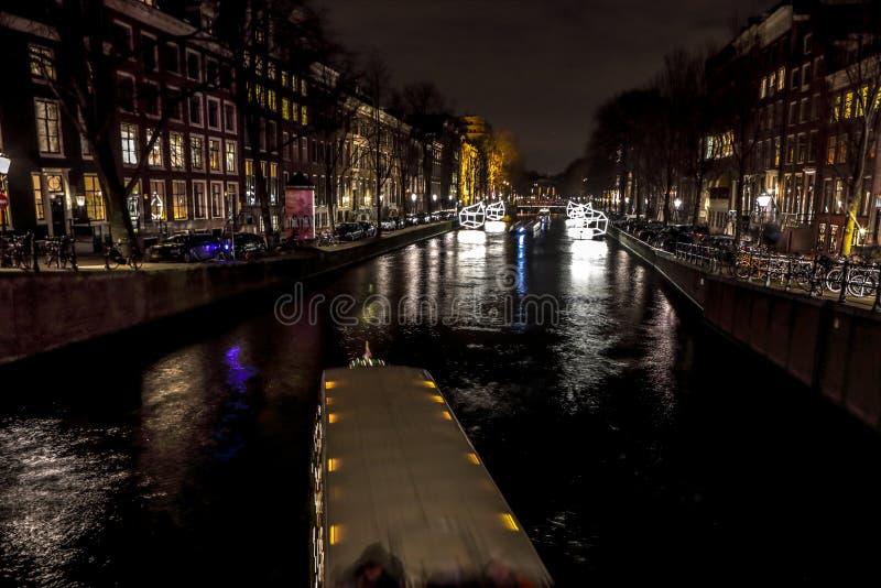Спешка шлюпок круиза в каналах ночи Светлые установки на каналы ночи Амстердама в пределах светлого фестиваля стоковые фотографии rf