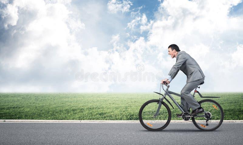 Спешность бизнесмена, который нужно работать на велосипеде стоковое фото