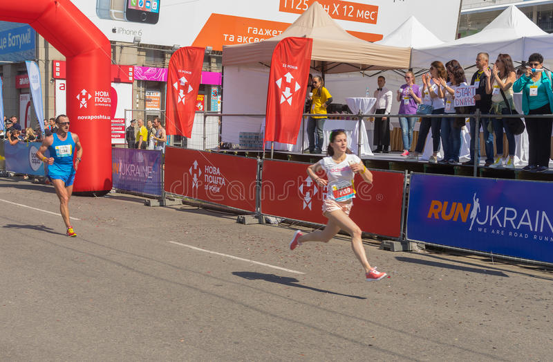 Спешность женщины к финишной черте во время гонки марафона Interipe Dnipro половинной на улице города стоковые фото
