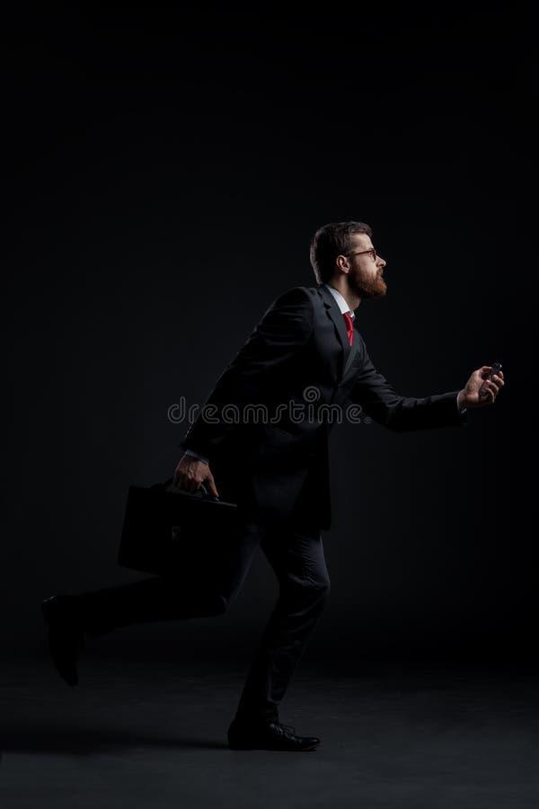 Спешность хода бизнесмена на черной предпосылке стоковое фото