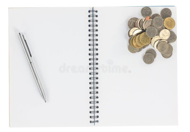 Спиральная тетрадь с изолятом монеток стоковая фотография rf