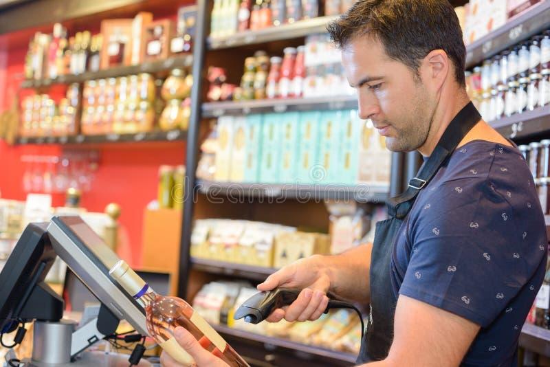 Спирт бутылки скеннирования клерка магазина стоковые фото