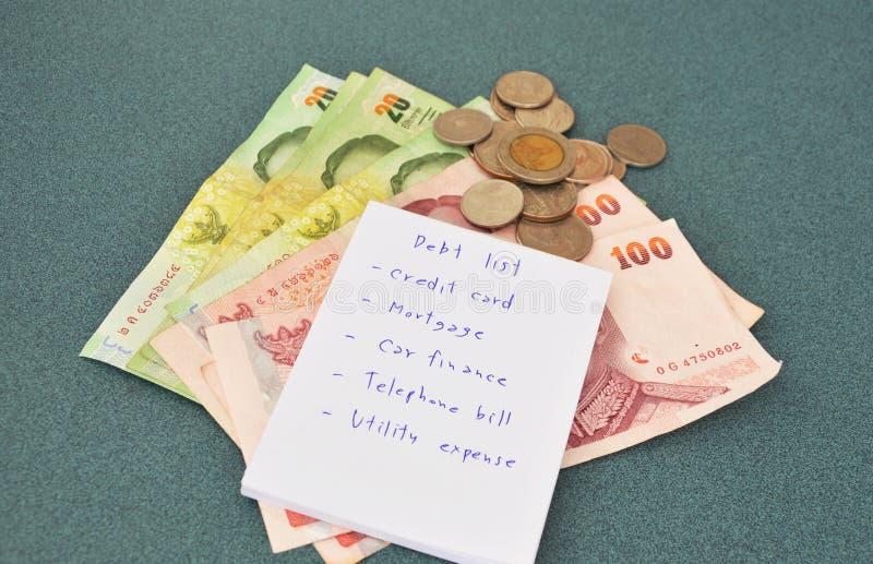 Список задолженности и тайские деньги на таблице стоковые изображения rf