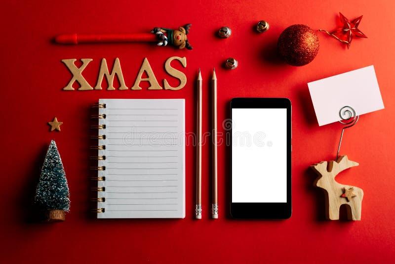 Список покупок рождества и мобильный телефон, праздник планируя красное украшение предпосылки, тетради и рождества стоковая фотография