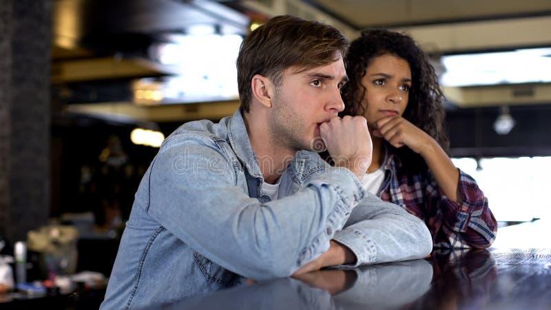Спичка спорта многонациональных пар наблюдая на большом экране в баре, осадила с результатами стоковые фотографии rf