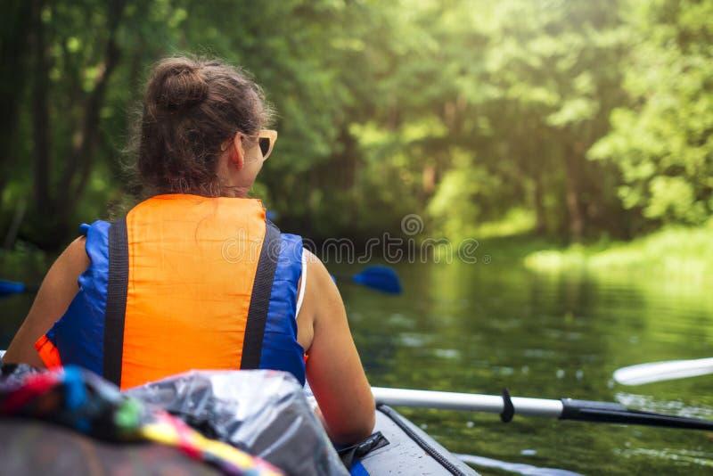 Сплавляться и canoeing Молодая женщина в шлюпке с заплывами весел на диком реке в джунглях Туристская девушка в каноэ с веслом стоковые изображения