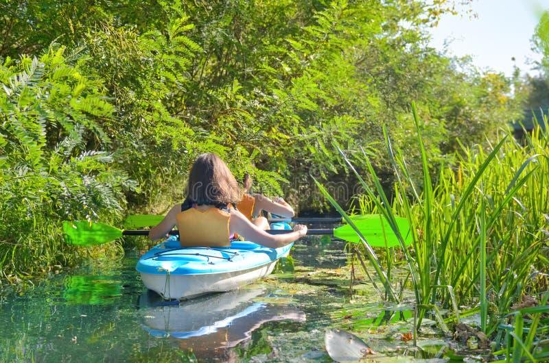 Сплавляться, мать и дочь семьи полоща в каяке на путешествии каное реки имея потеху, активные выходные осени с детьми стоковые изображения