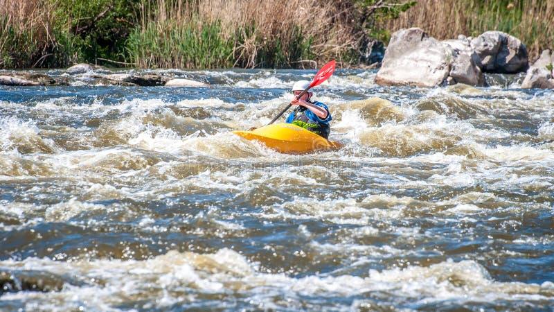 Сплавлять, сплавляться Неопознанный человек плавает на его коротком каяке whitewater кинжала Экологический туризм воды стоковые фото