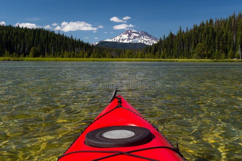 Сплавляясь на каяке красивое озеро летом к горному пику стоковые фото