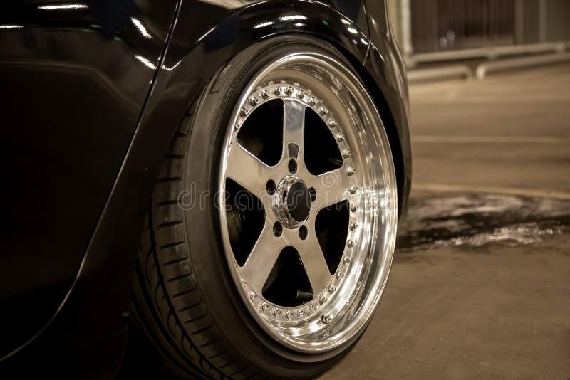 Сплавьте отполированные оправы автомобиля спорт Широкие колеса с протягиванными автошинами Настроенный низкий автомобиль стоковые изображения rf