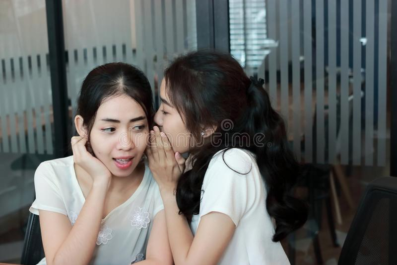 Сплетня молодой азиатской женщины шепча в живущей комнате стоковое фото rf