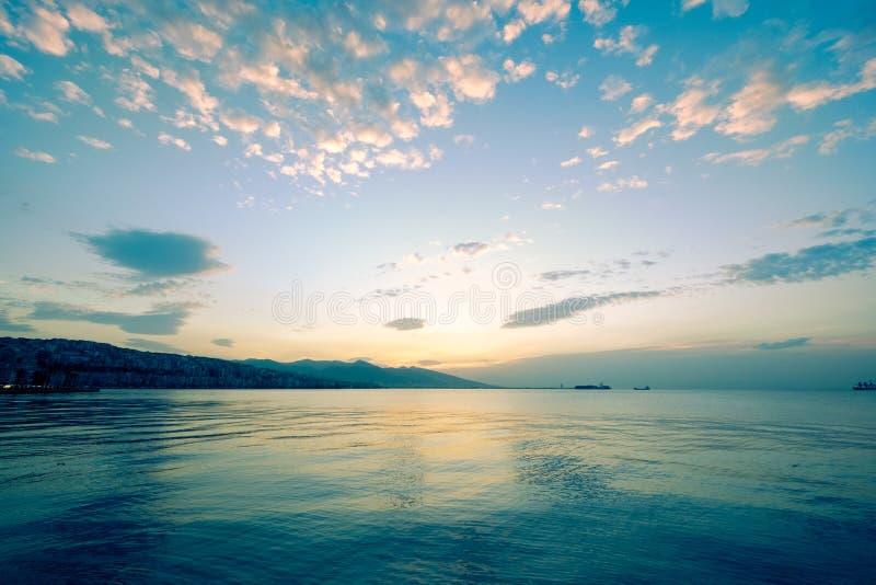 Спокойная вода, голубое небо и славные облака стоковые изображения rf