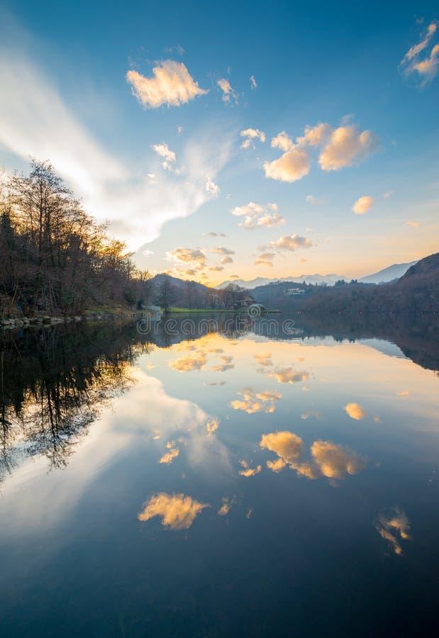 Спокойная вода озера, отражения облачного неба, цвета захода солнца стоковые фото