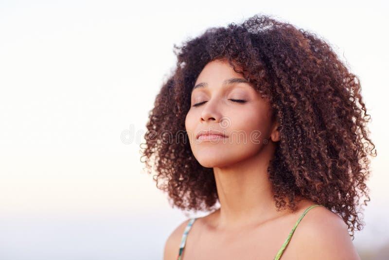 Спокойная женщина смешанной гонки с ей глаза закрыла outdoors стоковое фото