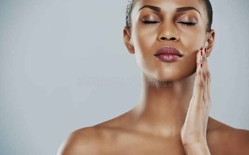Спокойная женщина с закрытыми глазами и касающей щекой стоковая фотография rf