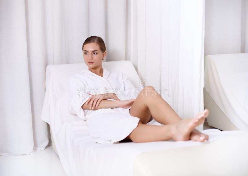 Спокойная молодая женщина ослабляя на deckchair в центре здоровья стоковая фотография