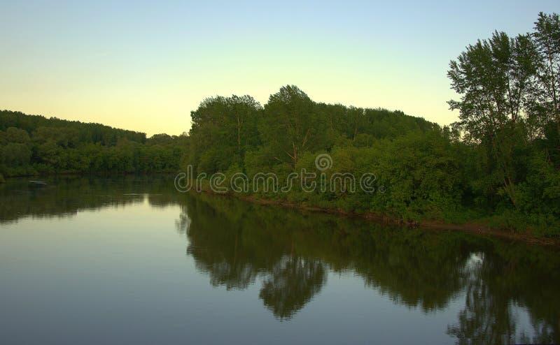 Спокойная подача реки леса отражает в своих водах лес на банках и небе E стоковое изображение