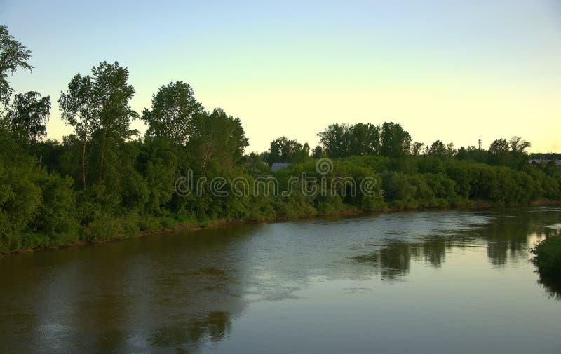 Спокойная подача реки с отражением облаков на заходе солнца E стоковые фотографии rf