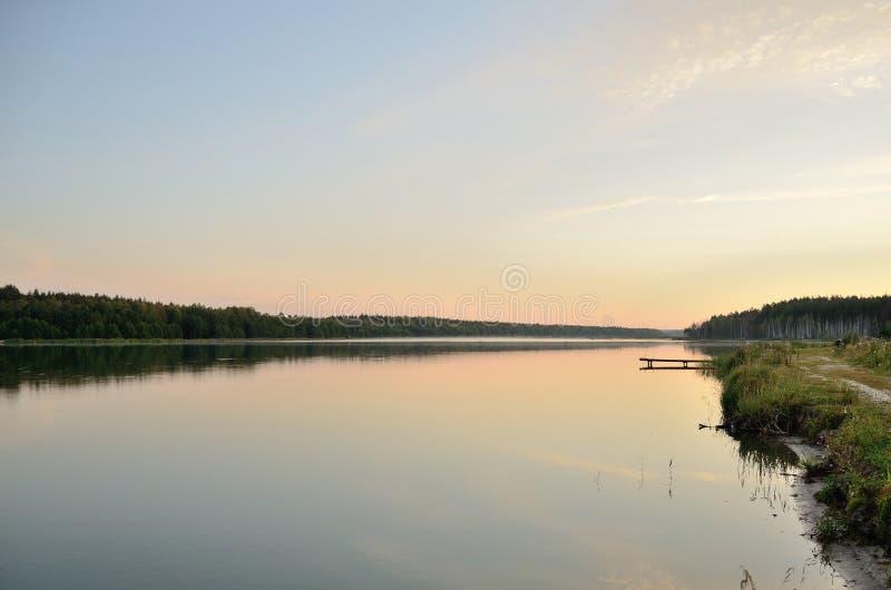 Спокойное озеро на зоре в windless погоде стоковое изображение