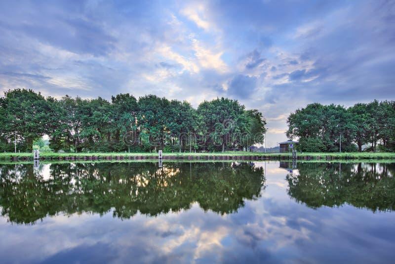 Спокойный ландшафт с каналом, деревьями, голубым небом и драматическими облаками, Тилбургом, Нидерландами стоковые изображения rf