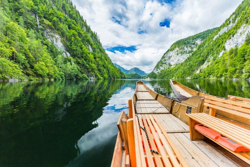 Спокойный вид на озеро горы Деревянная шлюпка и затишье мочат поверхностный и зеленый лес сосны стоковые изображения rf