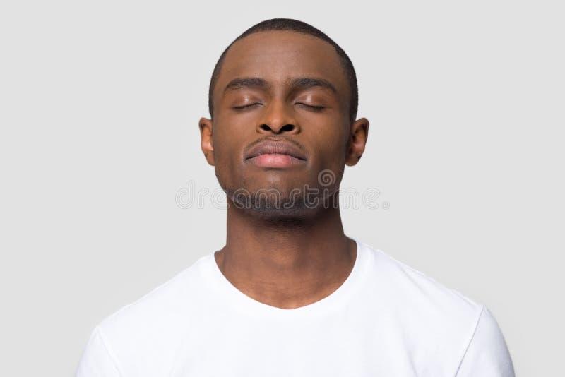 Спокойный заботливый Афро-американский человек наслаждается принять глубокий вдох стоковое изображение rf