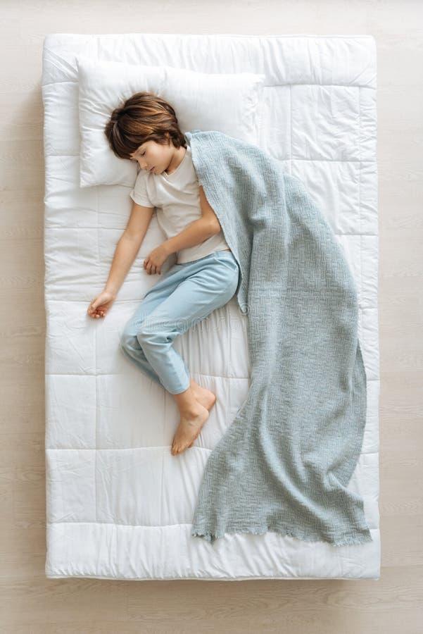 Спокойный мечтательный ребенк покрытый с голубым одеялом стоковое изображение rf