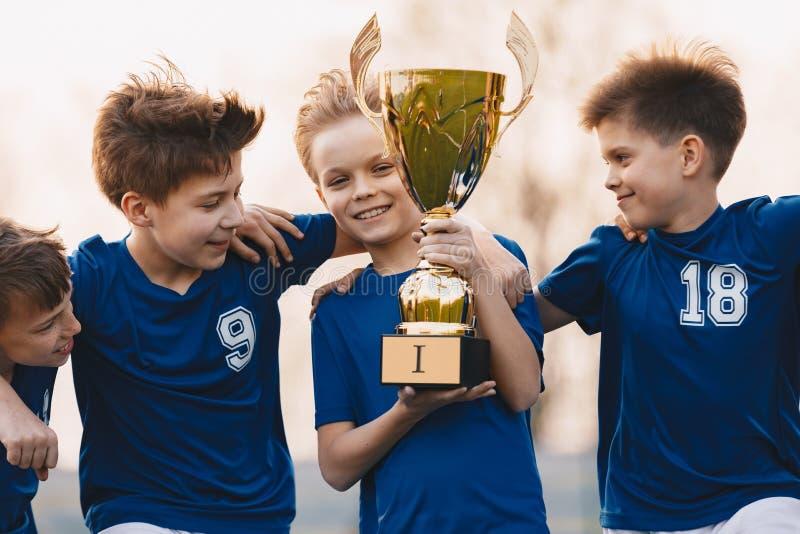 Спортивная команда мальчиков празднуя победу Счастливые дети держа золотой трофей Футбольная команда детей поднимая чашку победит стоковое изображение