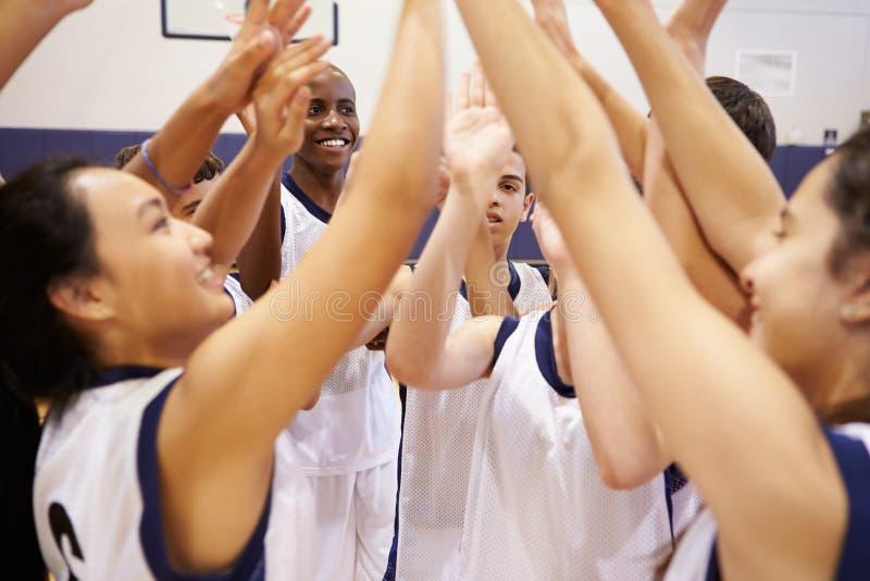 Спортивная команда средней школы празднуя в спортзале стоковое изображение rf