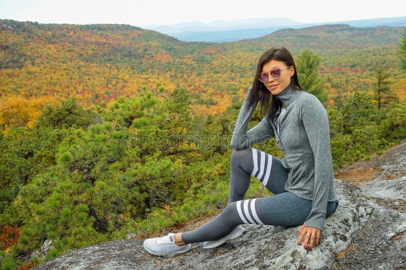 Спортивная молодая туристка наслаждается видом на осенний парк стоковое фото