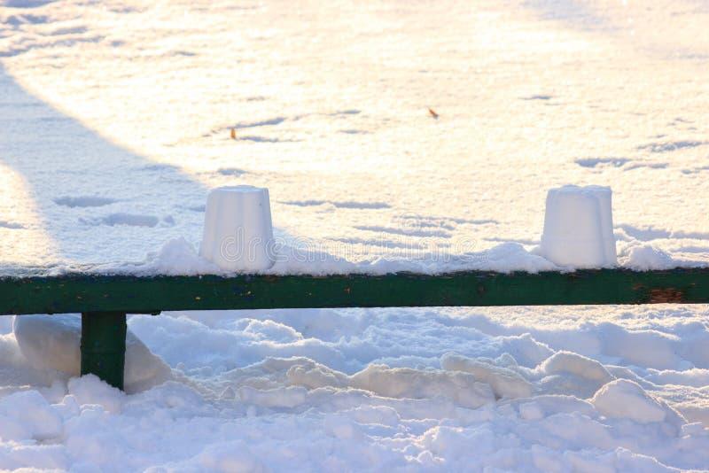 Спортивная площадка детей в зиме, качаниях и carousels под снегом на солнечный день отсутствие людей, пустой области, ждать стоковое изображение