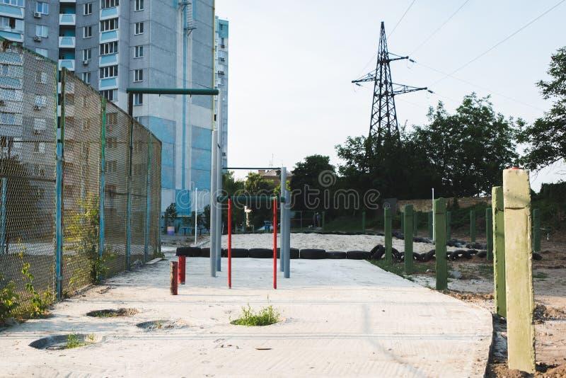 Спортивная площадка детей с качаниями во дворе  жилого дома в городе стоковые изображения