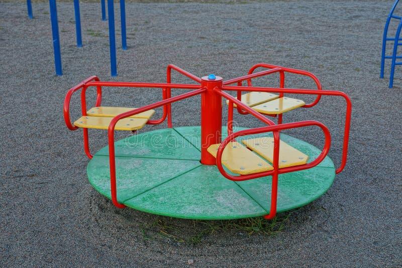 Спортивная площадка детей с кругом покрасила carousel на том основании в улице стоковая фотография