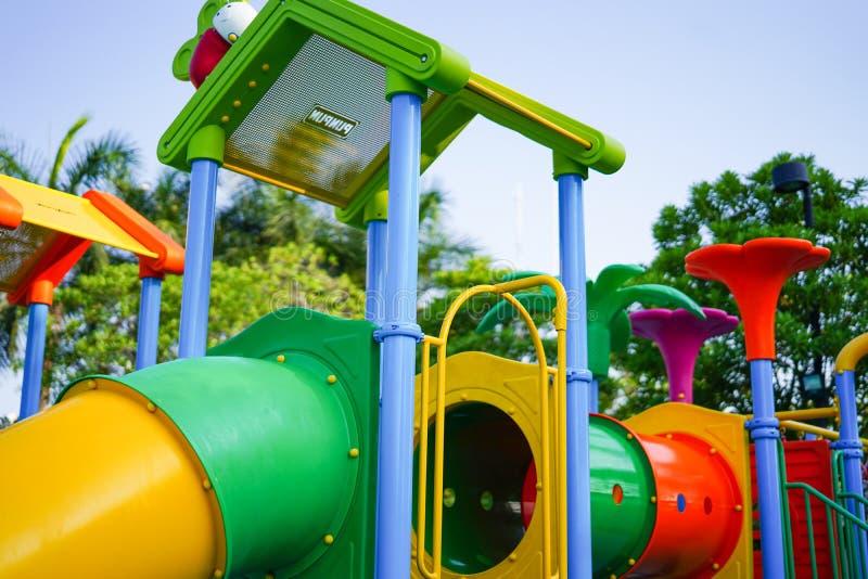 Спортивная площадка для детей ребенк имея потеху с красочным скольжением на деятельностях при двора стоковая фотография
