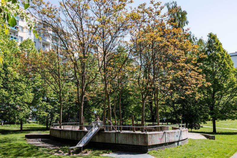 Спортивная площадка ` s детей в парке между жилыми домами в Берлине Marzahn, Германии стоковые фото