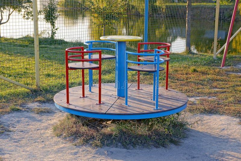 Спортивная площадка ` s детей с кругом покрасила carousel в траве стоковое изображение