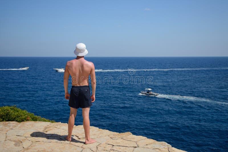 Спортивный молодой человек на скале смотрит на море стоковые фото